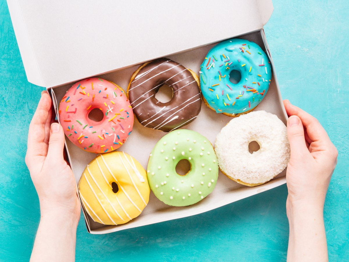 Female hands holding box with colorful donuts on blue concrete background
